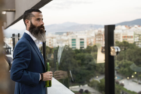 Bearded businessman standing on roof terrace with beer bottle looking at distance - JASF001034