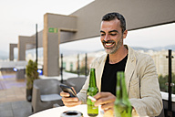 Portrait of smiling man standing on roof terrace with beer bottles and cigarette looking at cell phone - JASF001040