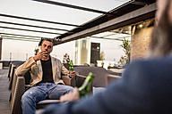 Man with beer bottle sitting on roof terrace smoking cigarette looking at his friend - JASF001043