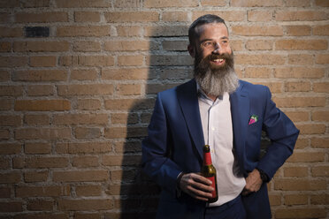 Portrait of happy businessman with beer bottle in front of brick wall - JASF001046