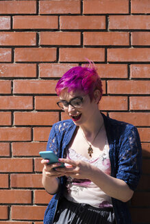 Amazed young woman with dyed hair looking at her cell phone - BOYF000464