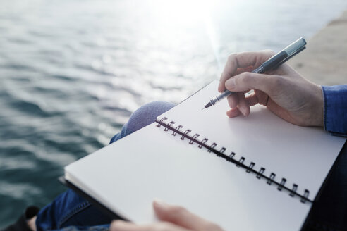Young woman sitting on dock writing in notebook - BOYF000494