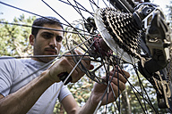 Man examining and adjusting the wheel of a mountainbike - ABZF000889