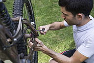 Man examining and adjusting the wheel of a mountainbike - ABZF000892