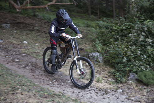 Mountainbiker riding downhill on forest path - ABZF000895