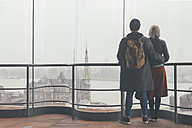 Belgium, Antwerp, back view of couple looking through window to docklands - RTBF000248