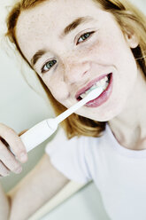 Portrait of smiling girl brushing teeth with electric toothbrush - JATF000878