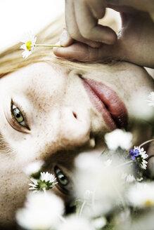 Smiling girl lying on field of flower, close-up - JATF000884