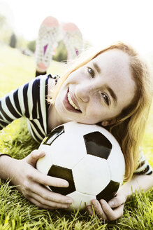 Portrait of smiling girl lying on a meadow with head on soccer ball - JATF000887