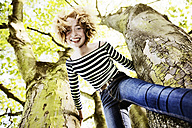Smiling girl climbing on a tree - JATF000890