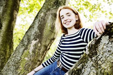 Portrait of smiling girl leaning against tree trunk - JATF000893