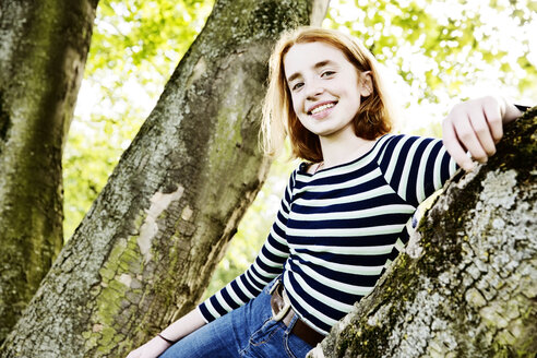 Portrait of smiling girl leaning against tree trunk - JATF000893
