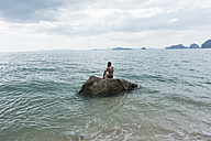 Thailand, Tubkaek, back view of woman sitting on rock looking at sea - JATF000900