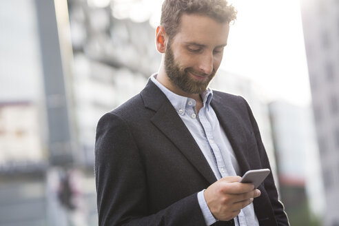 Smiling young businessman looking at cell phone outdoors - FKF001996