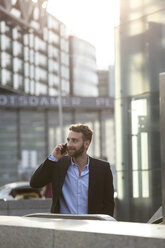 Young businessman on cell phone outdoors - FKF002011
