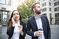 Businessman and businesswoman with cell phone and coffee to go outdoors - FKF002020