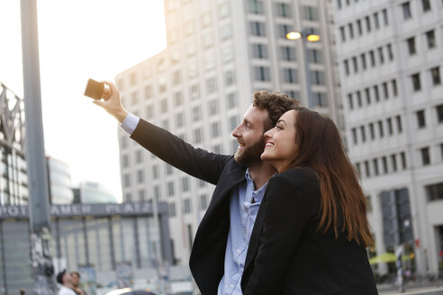 Smiling young businessman and businesswoman taking selfie outdoors - FKF002035