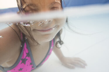 Little girl diving underwater in a paddling pool - JASF001049