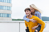 Happy young man carrying his girfriend piggyback - DIGF000846