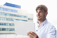 Young man holding digital tablet outdoors - DIGF000852