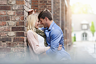 Happy couple in love leaning against brick building - DIGF000873