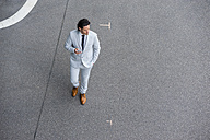 Walking businessman with smartphone crossing street - DIGF000906