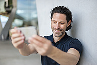 Portrait of smiling man taking selfie with cell phone - DIGF000909