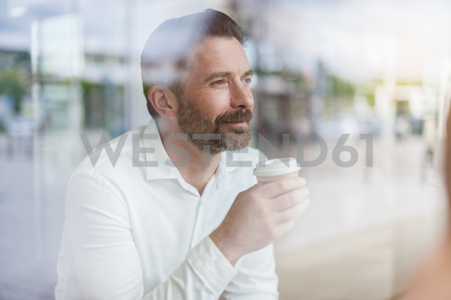 Portrait of relaxed businessman looking through window of coffee shop - DIGF000912