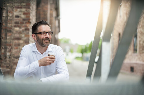 Smiling businessman with coffee to go - DIGF000915