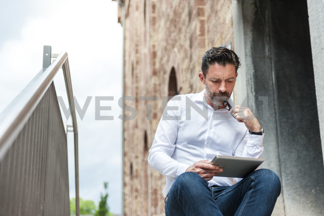 Businessman sitting on stairs looking at tablet - DIGF000930