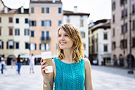 Portrait of smiling young woman with coffee to go - GIOF001356