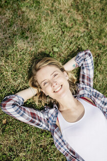 Portrait of smiling young woman relaxing on a meadow - GIOF001362