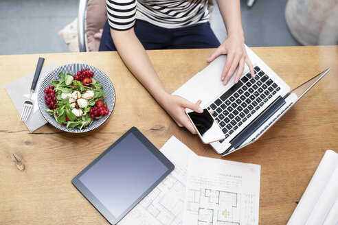 Woman at desk using laptop and cell phone next to construction plan and salad - REAF000112