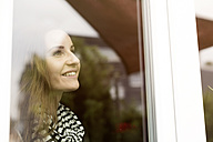 Young woman looking out of window, smiling - REAF000130