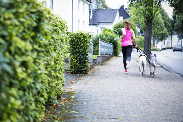 Young woman jogging with two dogs - REAF000142