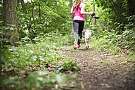 Young woman jogging with dog in forest - REAF000145