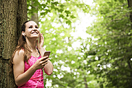 Sportive young woman with smartphone and earbuds - REAF000148