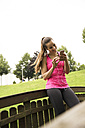 Sportive young woman with smartphone and earbuds - REAF000151
