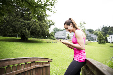 Sportive young woman with smartphone and earbuds - REAF000154