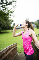 Sportive young woman drinking from bottle - REAF000157