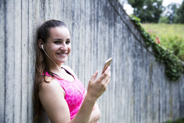 Sportive young woman with smartphone and earbuds - REAF000160
