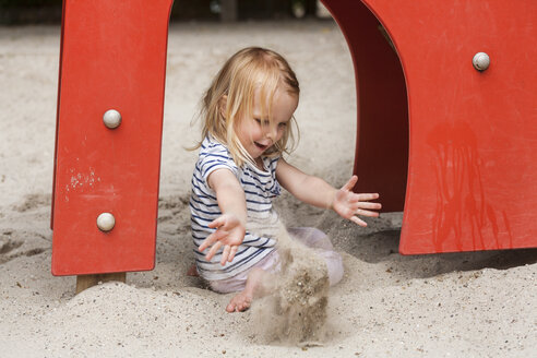 Blond little girl in sandbox on playground - TCF005069