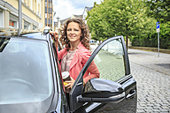Portrait of smiling woman getting on her car - VTF000542