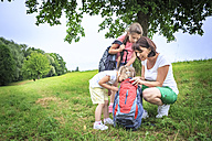 Mother and daughters on meadow during hiking, looking into backpack - VTF000548