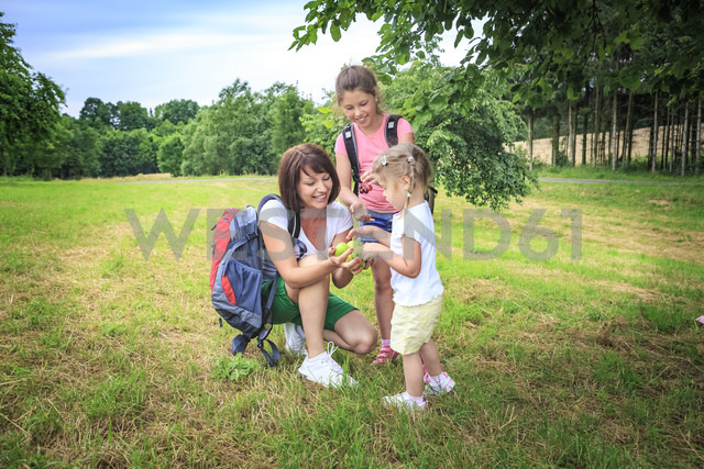 Mother giving apples, mother and daughters on meadow during hiking - VTF000551 - Val Thoermer/Westend61
