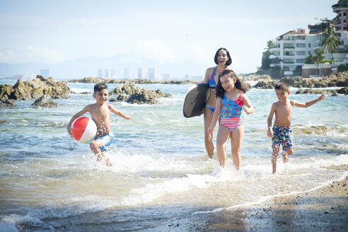 Mexico, Puerto Vallarta, mother and three children having fun at seafront - ABAF002065