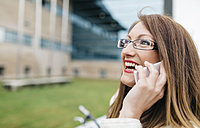 Portrait of laughing businesswoman with glasses talking by phone - DAPF000196