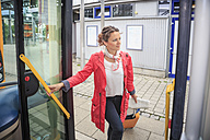 Young woman getting into bus - VTF000555