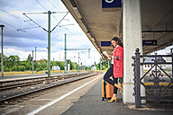 Germany, young woman at rail station in Sonneberg, reading newspaper - VTF000558