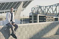 Fashionable businessman sitting on wall at sunlight - SKCF000132